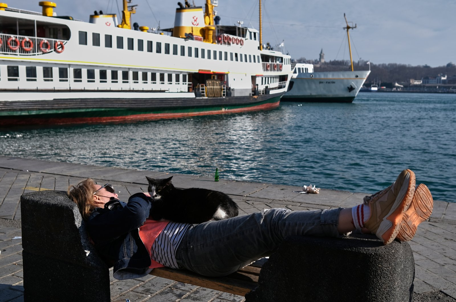A tourist takes a nap on a bench by the Bosporus during a local Sunday lockdown imposed to slow the rate of the coronavirus contagion in Istanbul, Turkey March 14, 2021. (Reuters Photo)