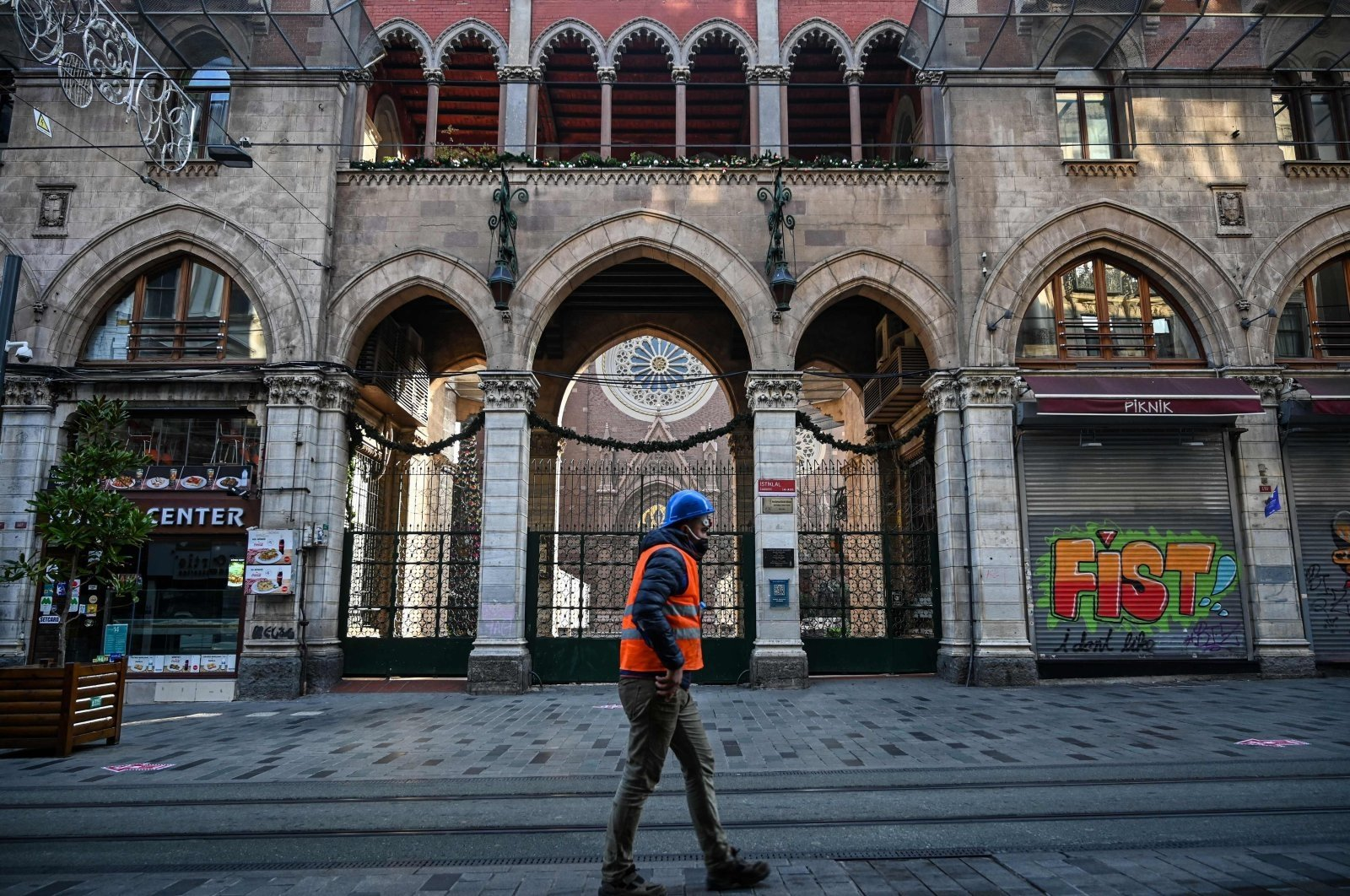 A construction worker walks down a deserted Istiklal Avenue in Istanbul during a weekend lockdown to curb the spread of COVID-19, Beyoğlu, Istanbul, Turkey, Dec. 5, 2020. (AFP Photo)
