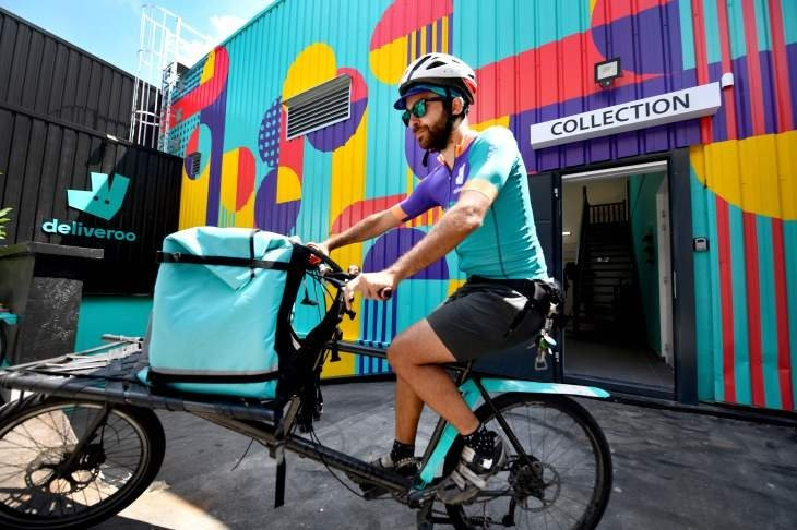 A biker working for the Food delivery service Deliveroo cycles off to deliver an order in Saint-Ouen, outside Paris, July 3, 2018. (AFP Photo)