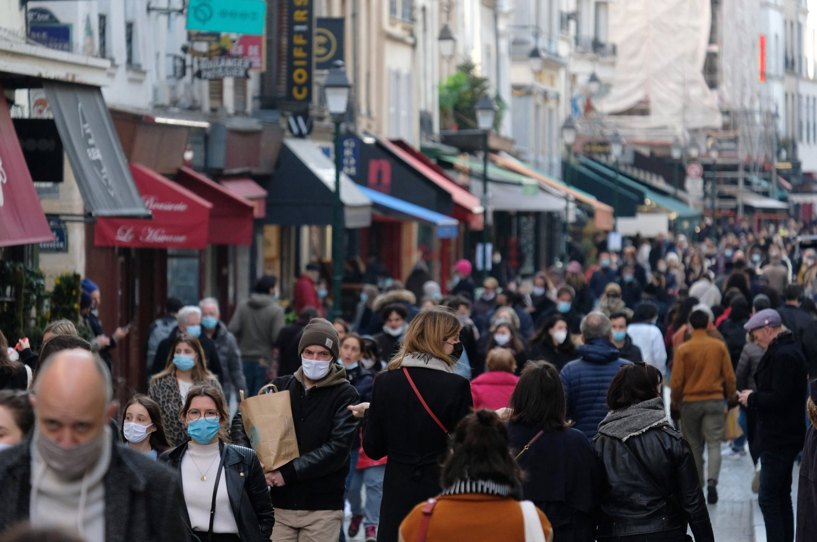 A crowd of people walk through a shopping strip on the first weekend of the third lockdown against the COVID-19 pandemic, as several parts of France enter a new partial lockdown. Paris, France, March 20, 2021. (Reuters Photo)