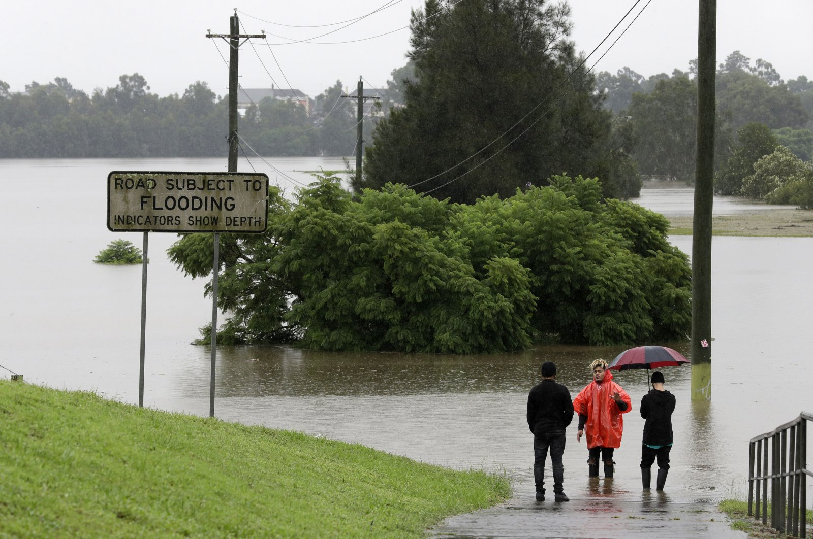 Men stand at the edge of a road flooded by water from the Hawkesbury River in Windsor, northwest of Sydney, New South Wales, Australia, March 22, 2021. (AP Photo)