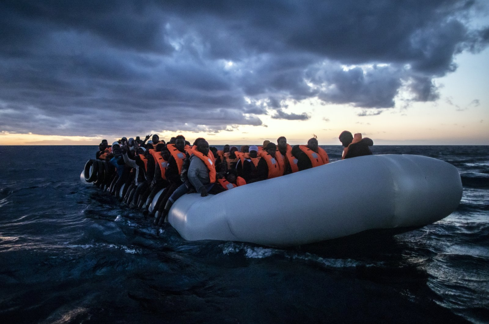 Migrants and refugees from various African nationalities wait on a rubber boat as aid workers on a rescue vessel of the Spanish NGO Open Arms approach in international waters in the Mediterranean Sea, 80 miles off the Libyan coast, Feb. 13, 2021. (AP Photo)