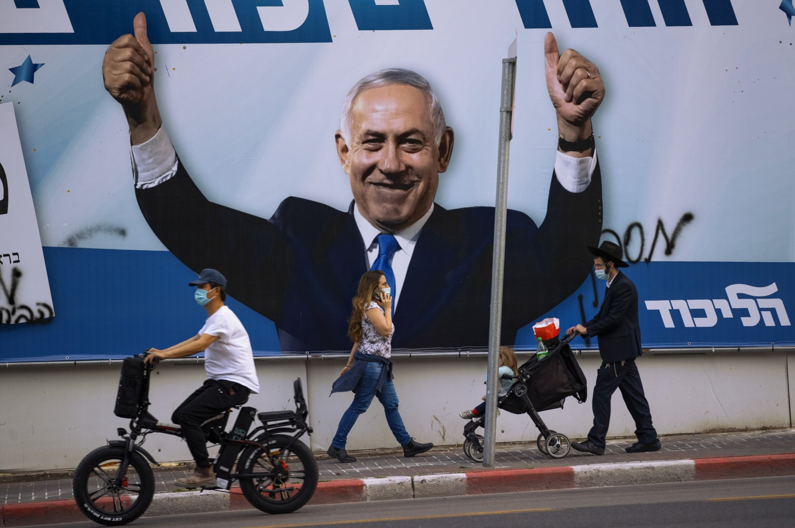 People pass an election campaign billboard for the Likud party that shows a portrait of its leader Prime Minister Benjamin Netanyahu, in Ramat Gan, Israel, March 21, 2021. (AP)