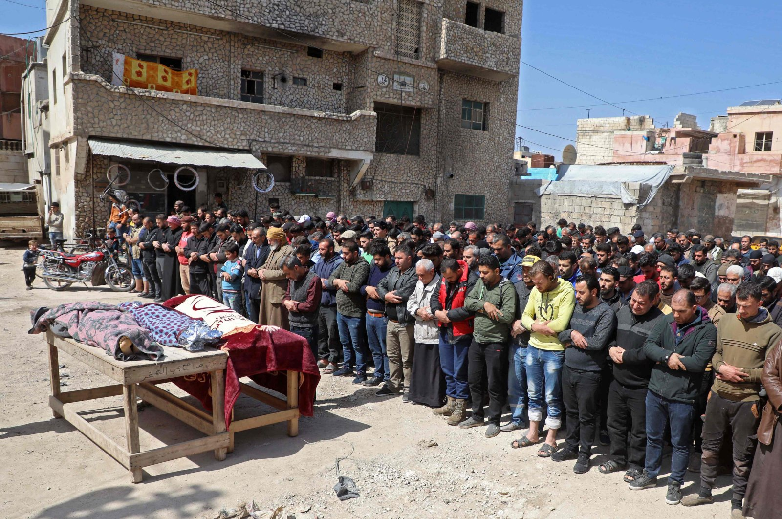 Mourners pray during a funeral in the village of Atareb in the northern province of Aleppo, Syria, March 21, 2021. (Photo by AAREF WATAD via AFP)