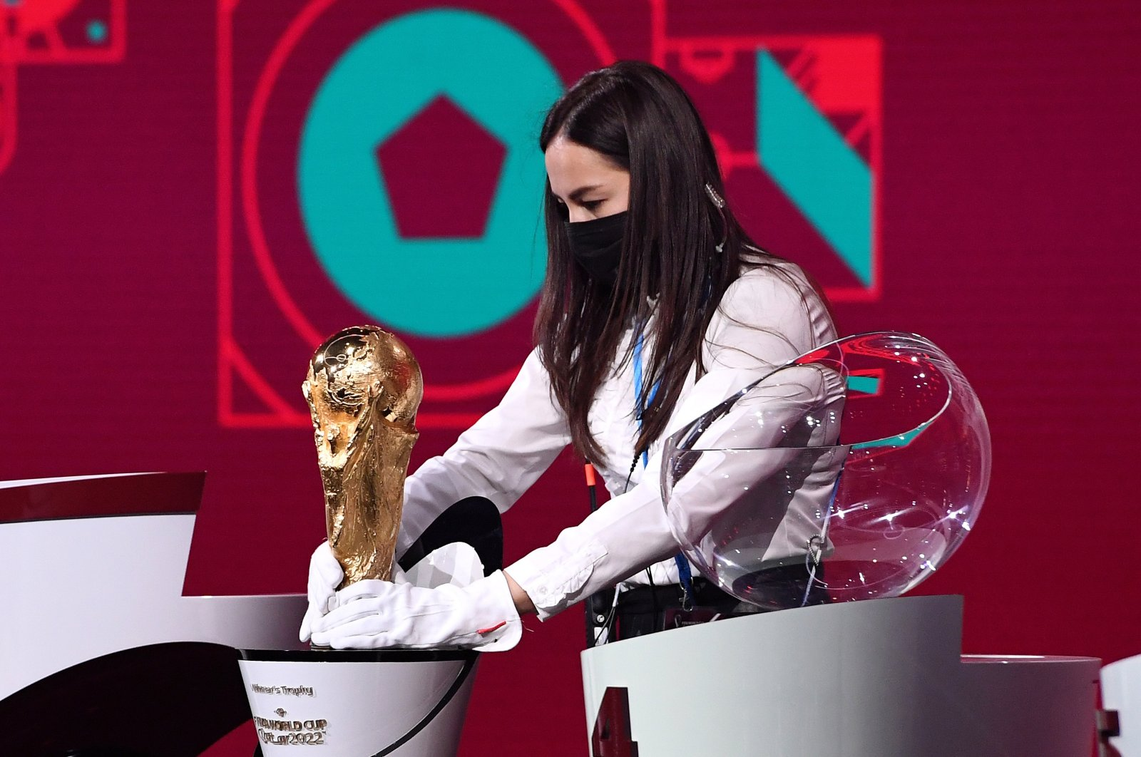 A member of staff cleans the World Cup Trophy prior to the Preliminary Draw of the 2022 Qatar FIFA World Cup, Zurich, Switzerland, Dec. 07, 2020. (Getty Images)