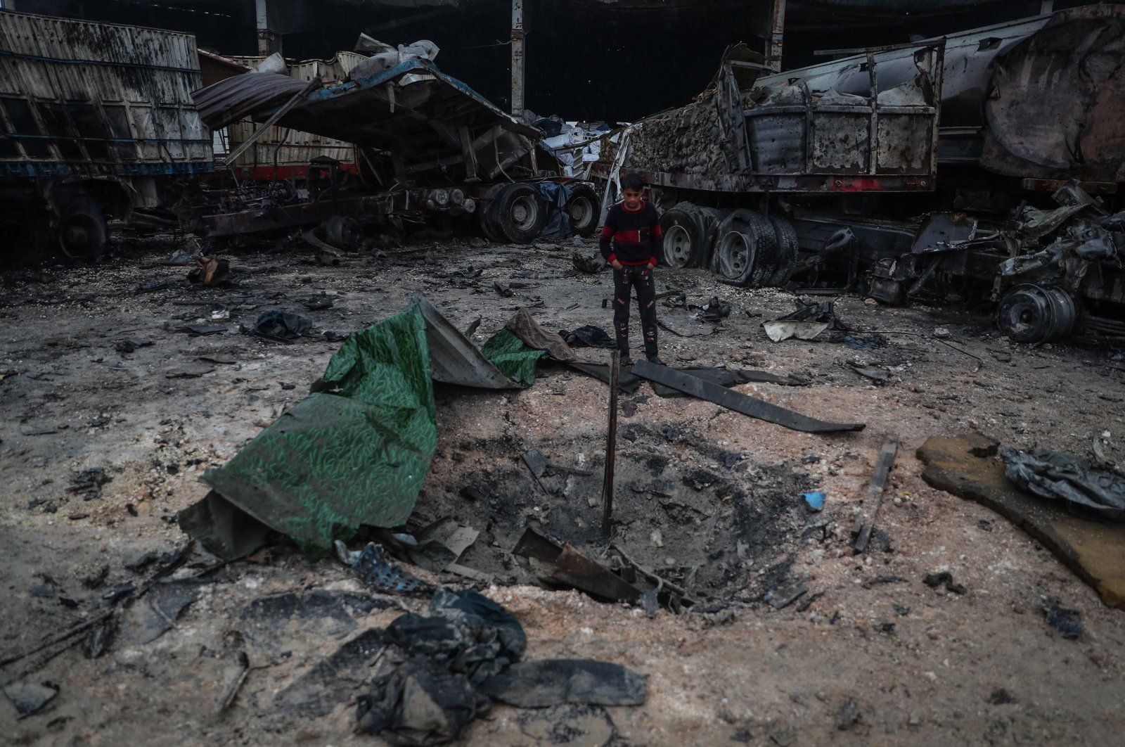 A Syrian child inspects the damage in the aftermath of an airstrike that was allegedly carried out by Russian warplanes on a truck depot near Bab al-Hawa border crossing on the Syrian-Turkish border, Idlib, Syria, March 22, 2021. (Getty Images)