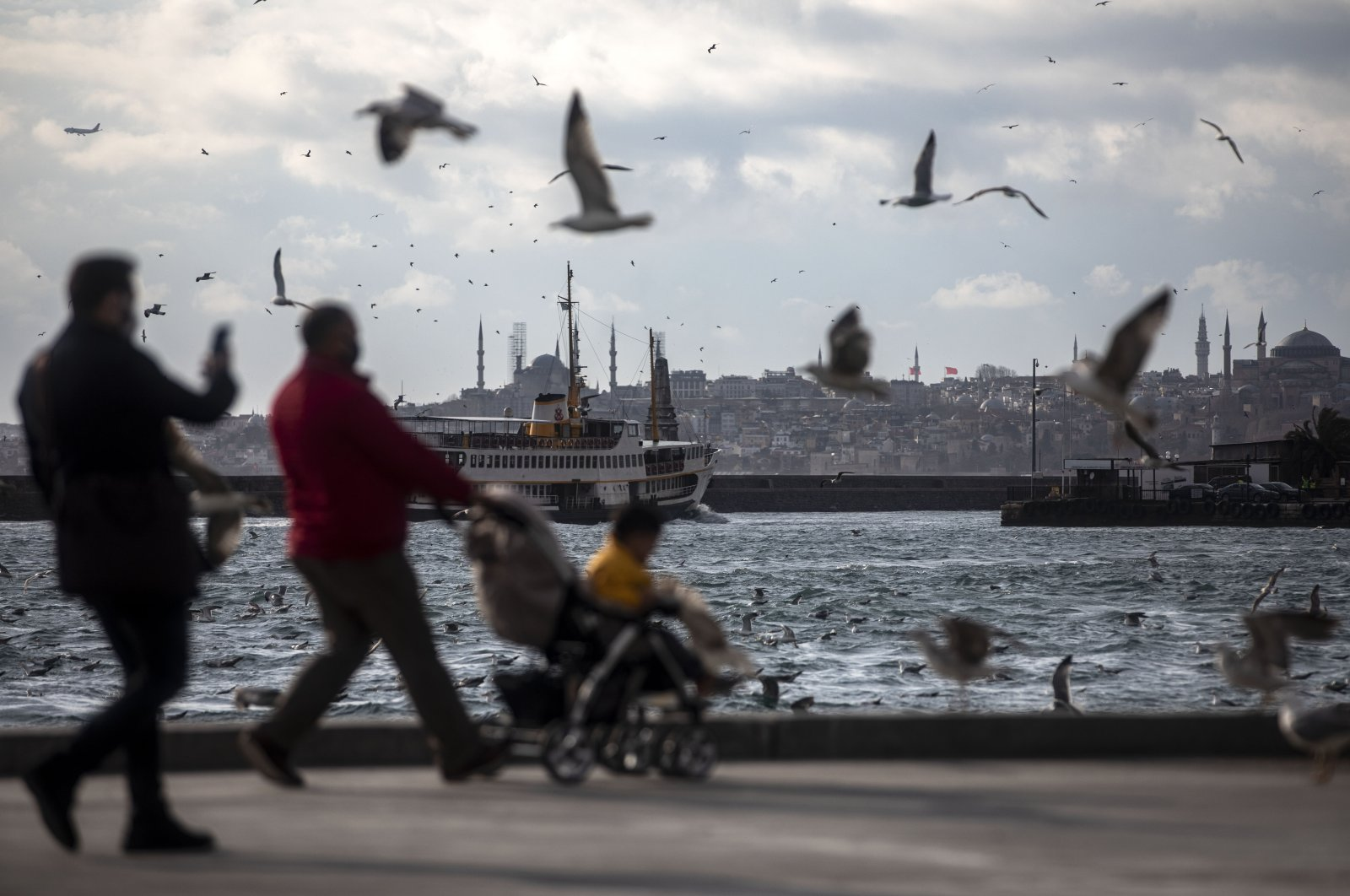 People walk along the Bosporus as seagulls fly above amid the coronavirus, Istanbul, Turkey, March 16, 2021. (Photo by Getty Images)