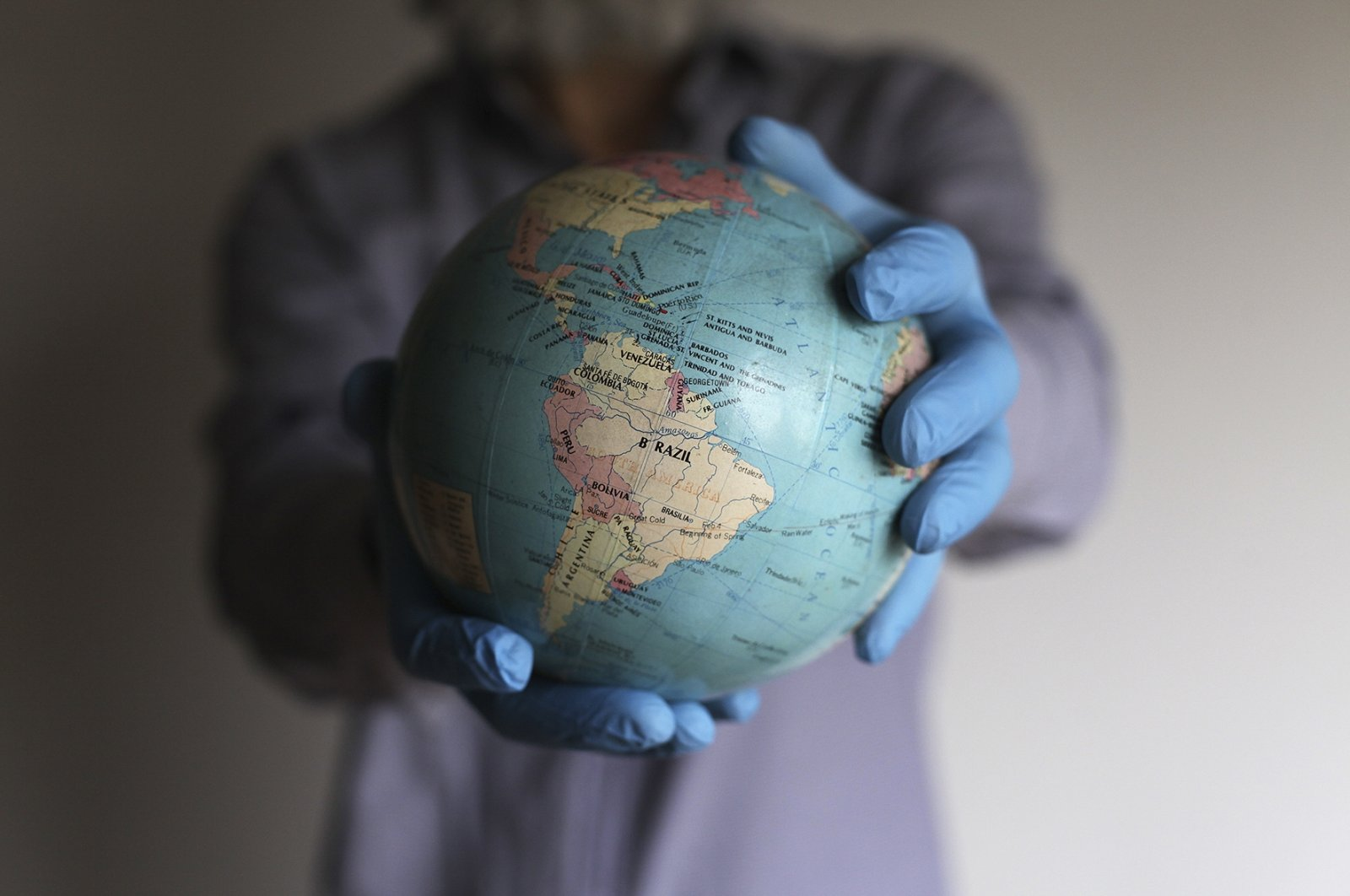 A man wearing medical gloves holds a globe in his hands, Buenos Aires, Argentina, Aug. 6, 2020. (Getty Images)