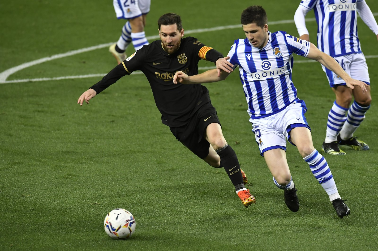 Barcelona's Lionel Messi (L) fights for the ball against Real Sociedad's Igor Zubeldia during the Spanish La Liga match at Reale Arena stadium, San Sebastian, Spain, March. 21, 2021. (AP Photo)