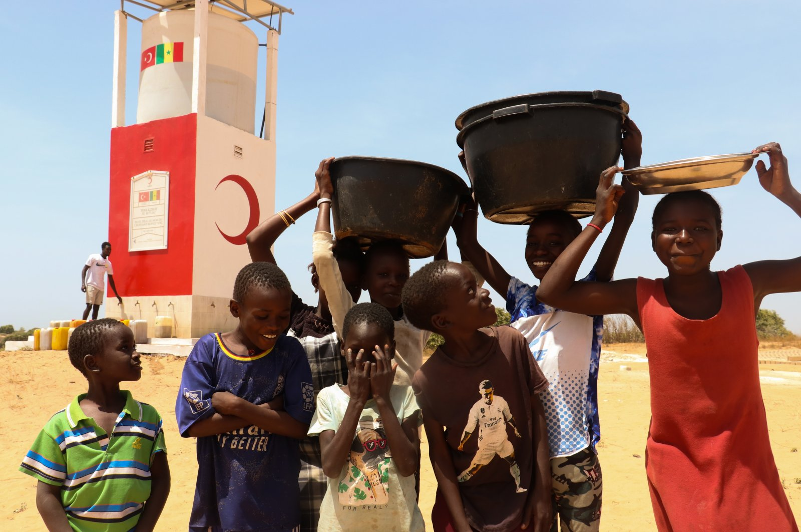 Children carrying water pose in front of a well being built by the Turkish Red Crescent, in Thies, Senegal, March 22, 2021. (AA PHOTO)
