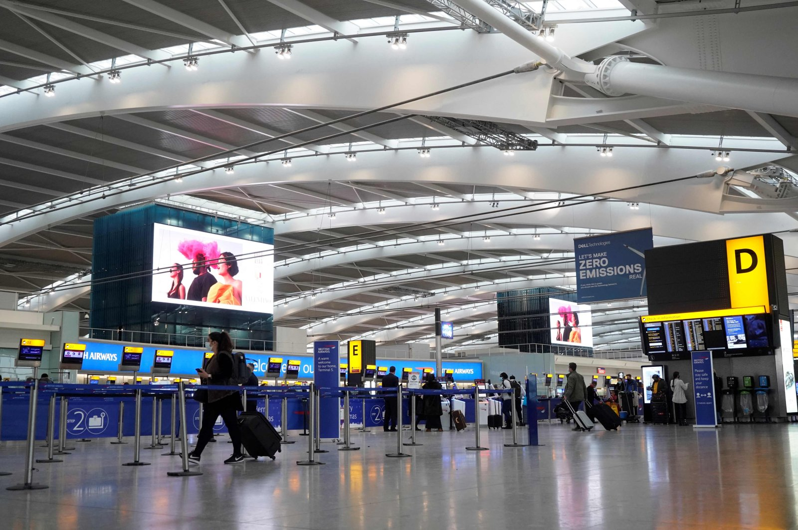 Travelers wearing face coverings walk with their luggage in the almost deserted departures hall at Terminal 5 of Heathrow Airport in west London, U.K., Dec. 21, 2020. (AFP Photo)