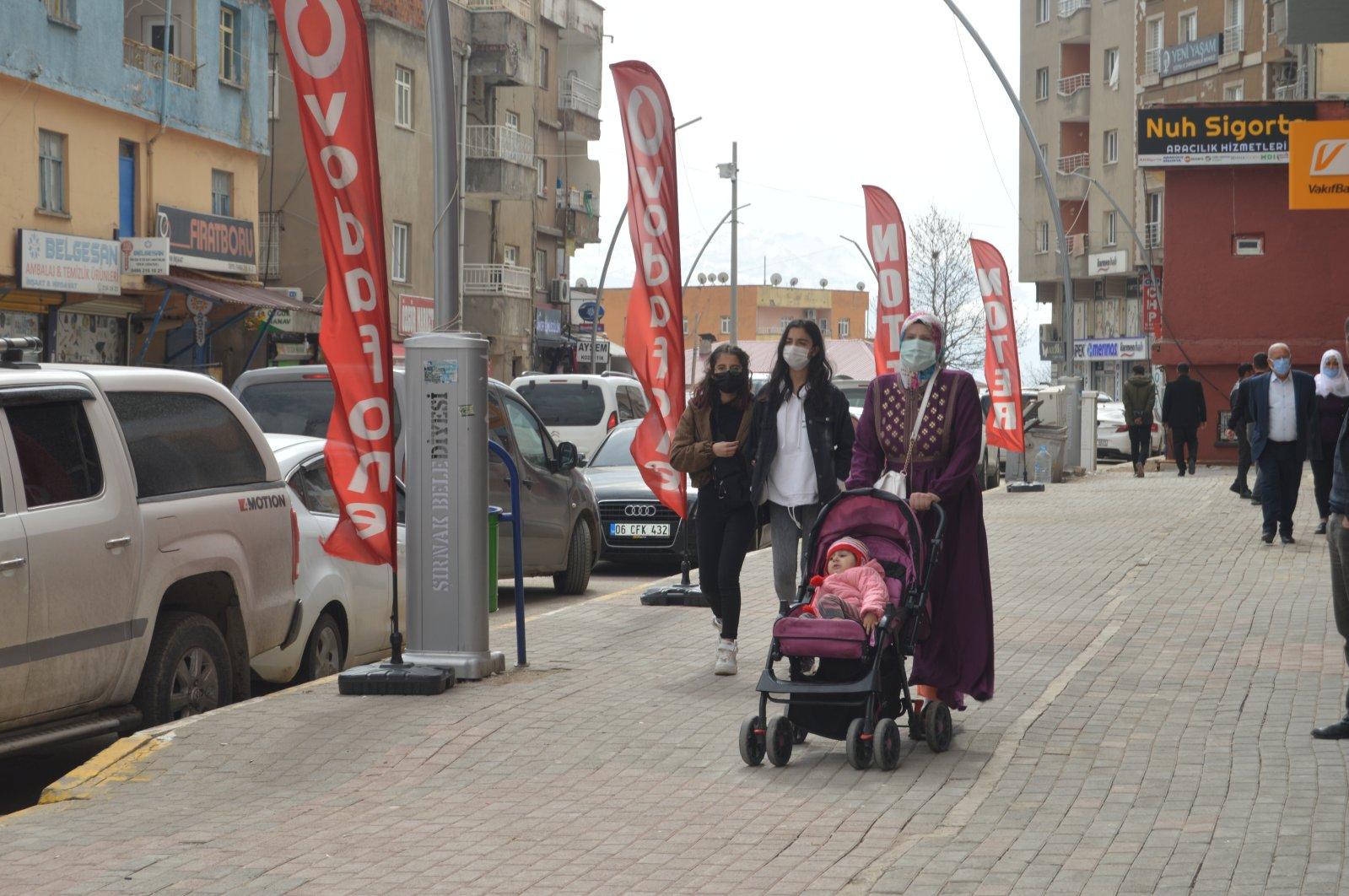People wearing protective masks walk on a street in Şırnak, southeastern Turkey, March 17, 2021. (AA PHOTO)