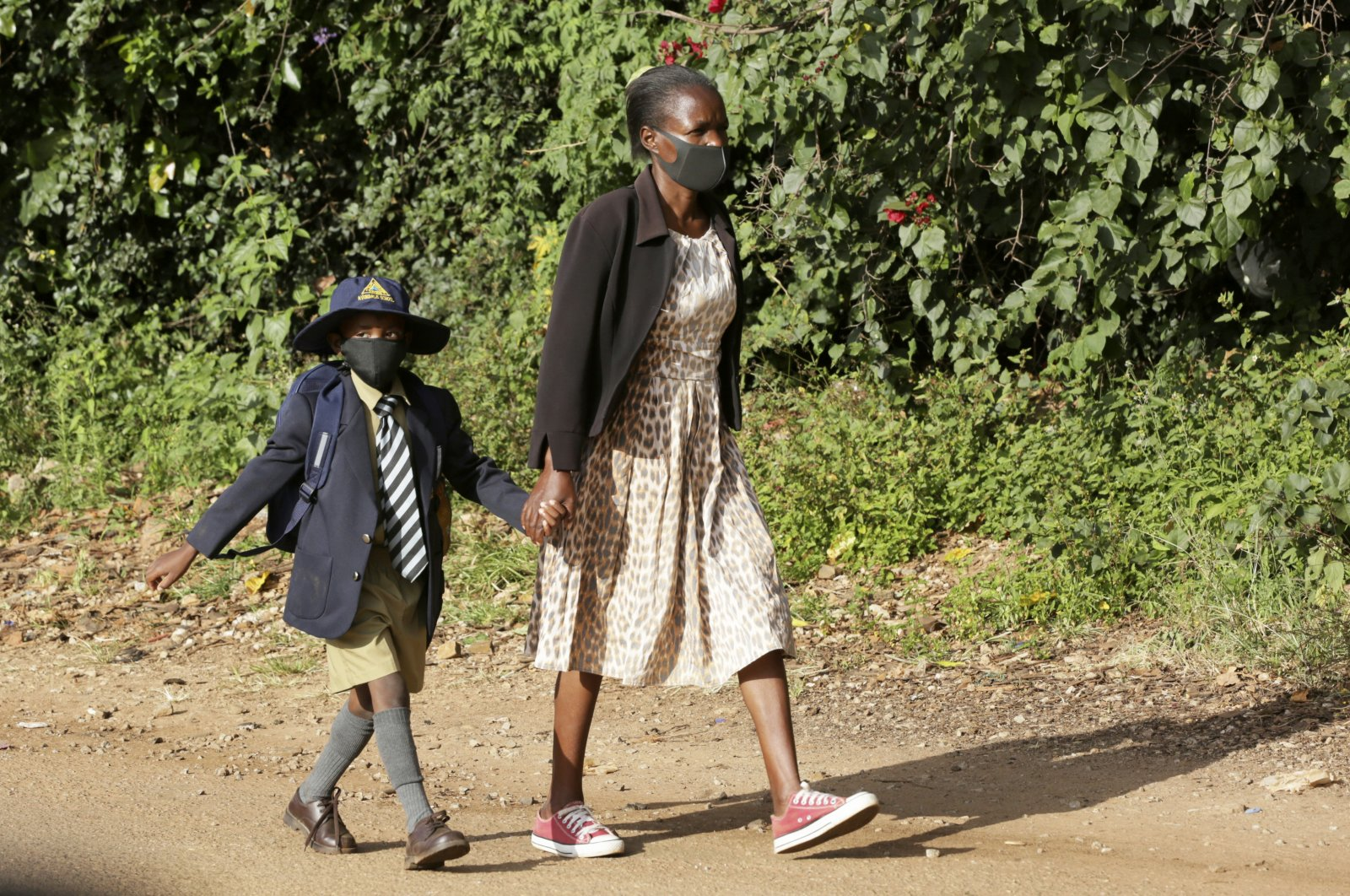 A child wears a face mask to curb the spread of COVID-19 on his way to school following the reopening of schools in Harare, Zimbabwe, March 22, 2021. (AP Photo)