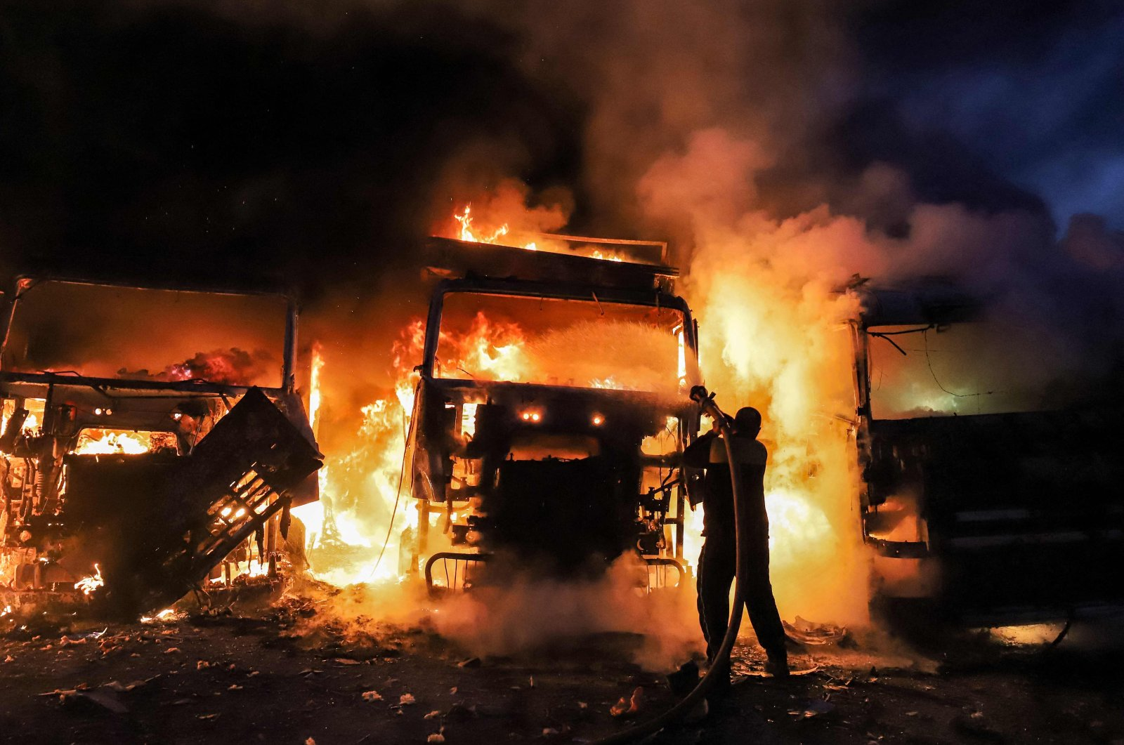 Members of the Syrian civil defense try to put out several trucks and freight vehicles on fire in the aftermath of airstrikes at a depot near the Bab al-Hawa border crossing between Syria and Turkey in the opposition-held northwestern Idlib province, Syria, March 21, 2021. (AFP)