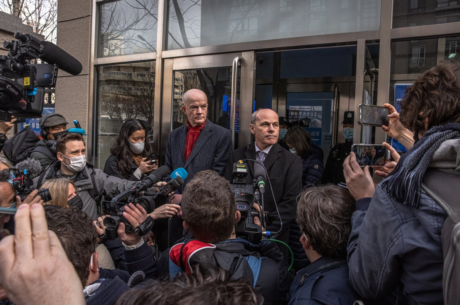Jim Nickel (C-R), deputy head of the Canadian embassy in Beijing and William Klein (C-L), acting deputy chief of the U.S. Embassy in Beijing, speak to the media at the entrance to the Intermediate People's Court in Beijing, China, 22 March 2021. (EPA Photo)