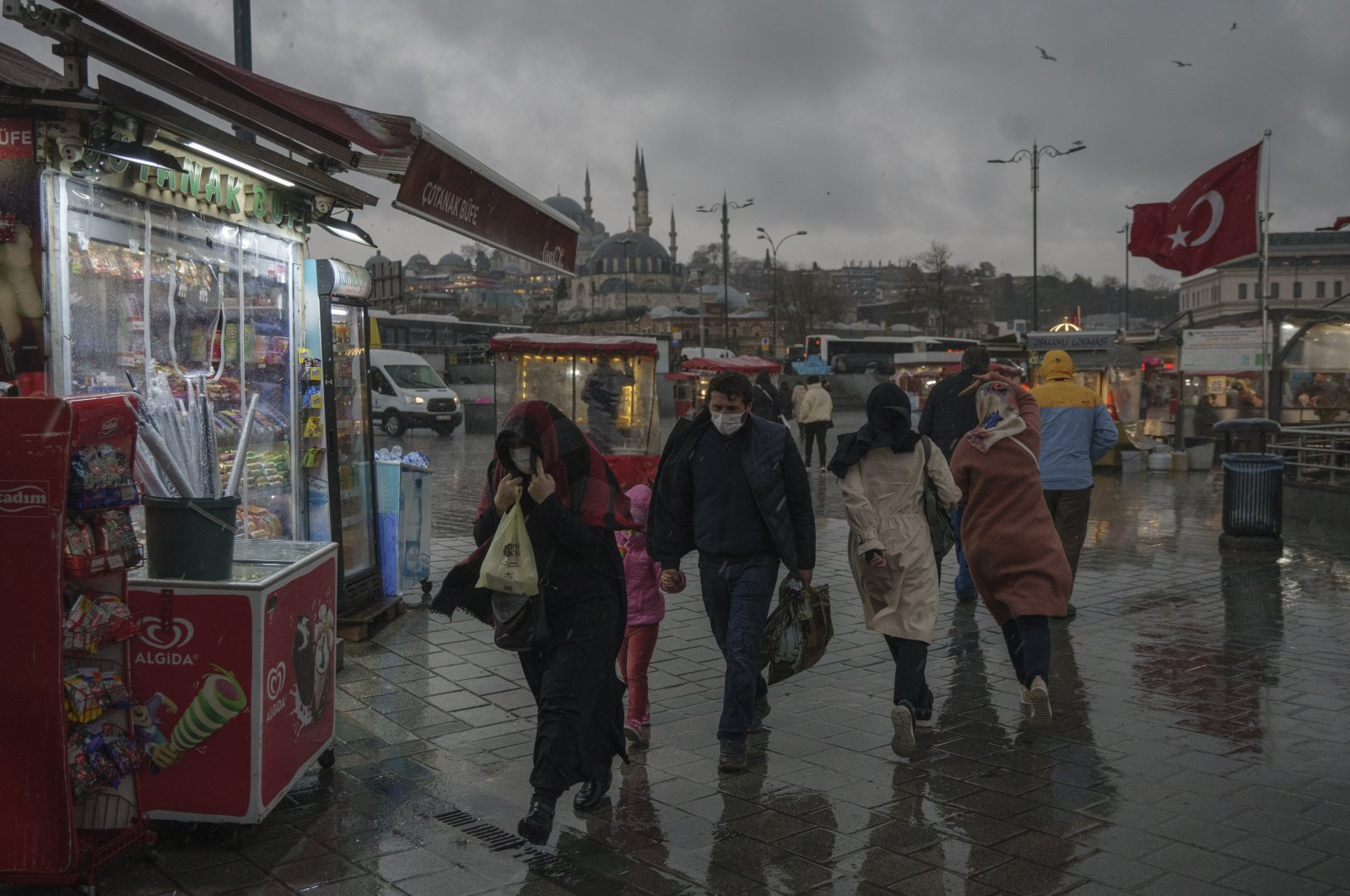 People walk during heavy rainfall in Istanbul's historic Eminönü district on Mar. 22, 2021 (DHA Photo)