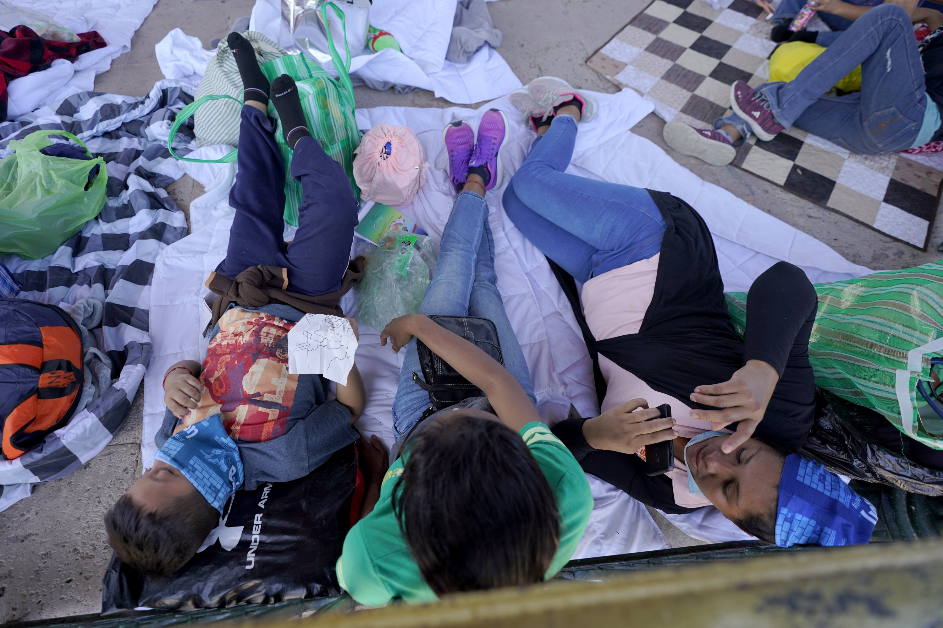 Migrants rest in a gazebo at a park after a large group of deportees were pushed by Mexican authorities off an area they had been staying after their expulsion from the U.S., in Reynosa, Mexico, March 20, 2021. (AP Photo/Julio Cortez)
