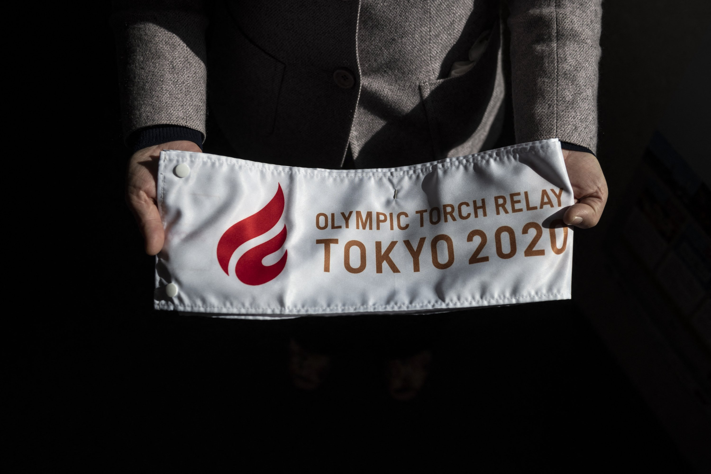 Tokyo 2020 Olympic torch relay runner Yumiko Nishimoto holds a Tokyo 2020 banner at a community center in Hirono, Fukushima Prefecture, Japan, Feb. 28, 2021.