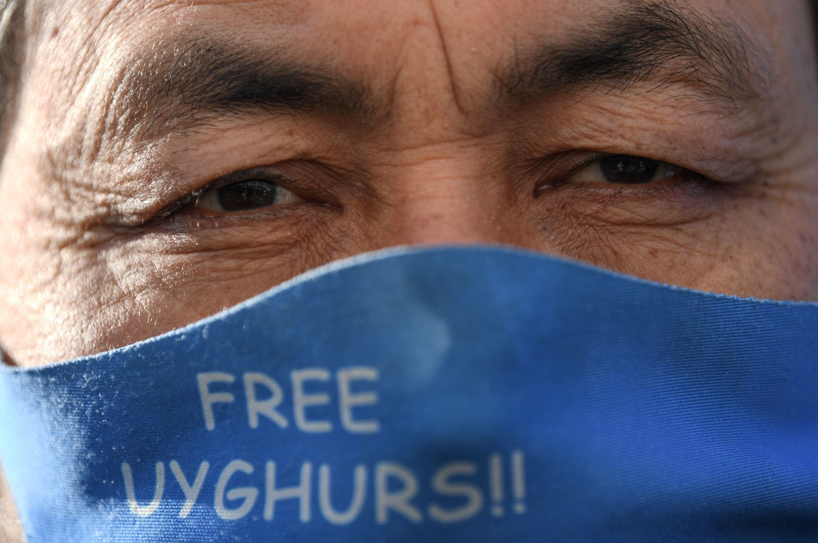 A member of the Uyghur minority wears a face mask to protect against the spread of the coronavirus as they demonstrate near China's consulate in Istanbul, Turkey, Feb. 22, 2021. (AFP Photo)