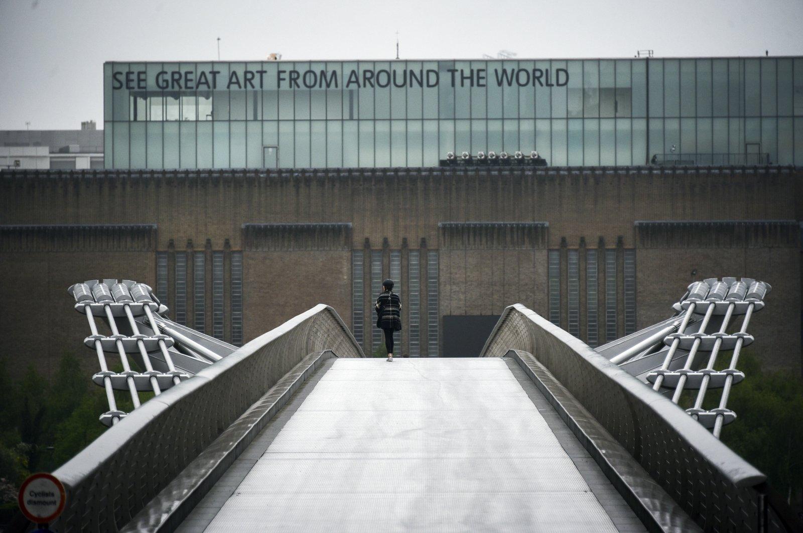 A woman walks on the nearly deserted Millennium Bridge as the rain falls, on the sixth week of lockdown due to the coronavirus outbreak, London, the U.K., April 28, 2020. (AP Photo)