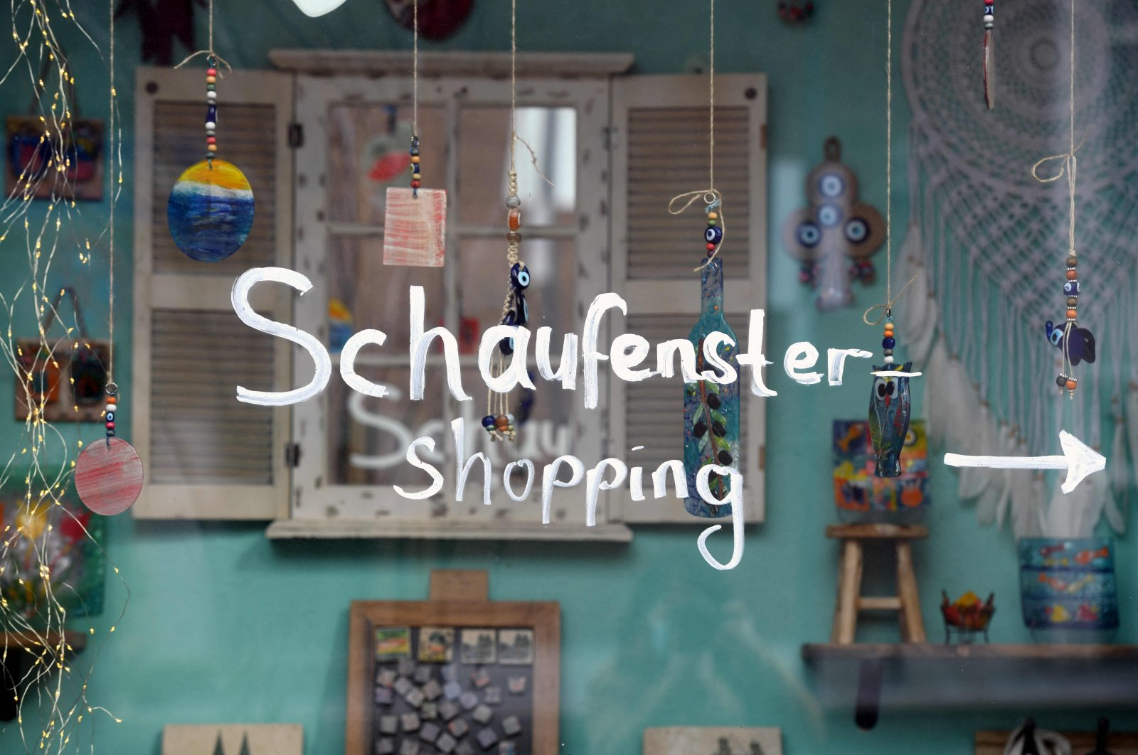 """A note saying """"window shopping"""" is written on a closed shop during the ongoing coronavirus pandemic in the city of Cologne, western Germany, March 12, 2021. (AFP Photo)"""