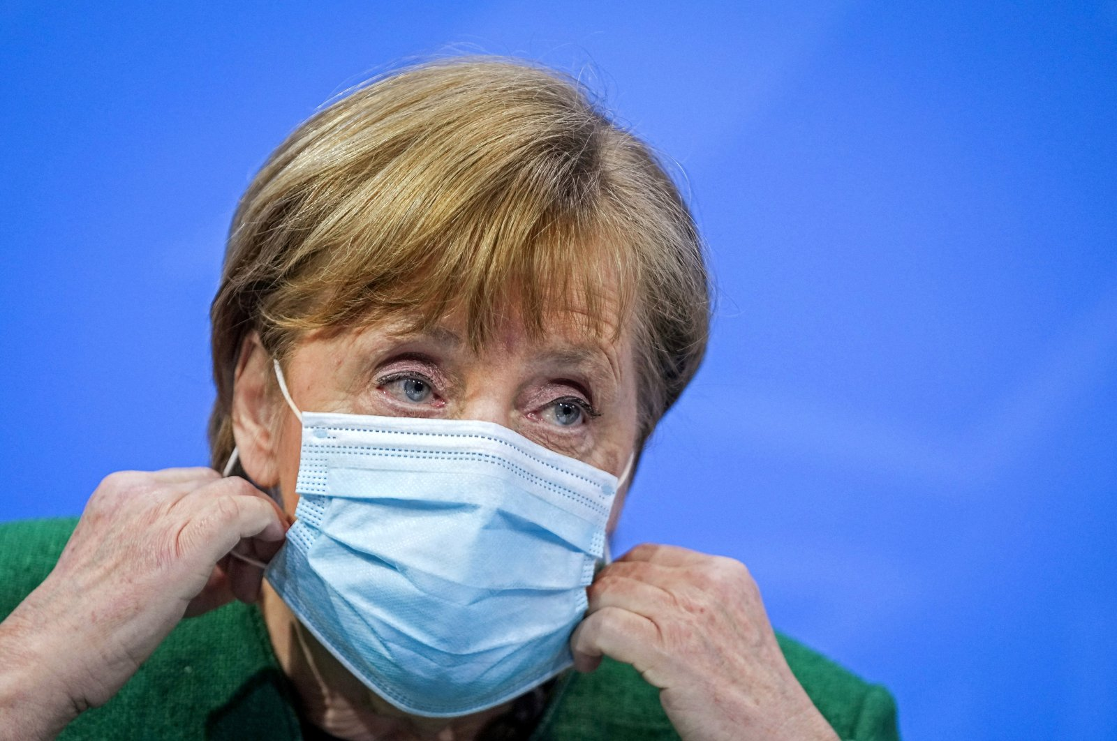 German Chancellor Angela Merkel holds her mask at a news conference after a meeting with state leaders to discuss options beyond the end of the pandemic lockdown, amid the outbreak of COVID-19, in Berlin, Germany, March 23, 2021. (Reuters Photo)