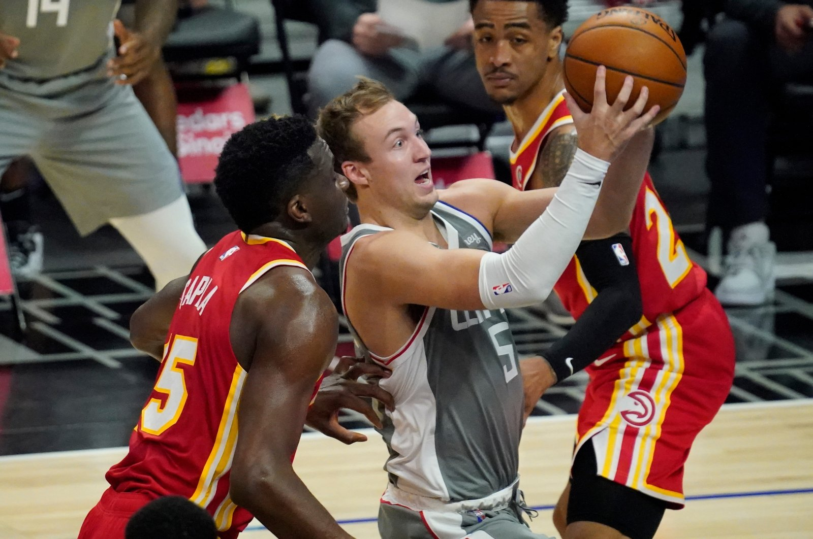 LA Clippers guard Luke Kennard (C) moves to the basket past Atlanta Hawks center Clint Capela (L) and forward John Collins (R) during an NBA match at Staples Center, Los Angeles, California, March 22, 2021. (Reuters Photo)
