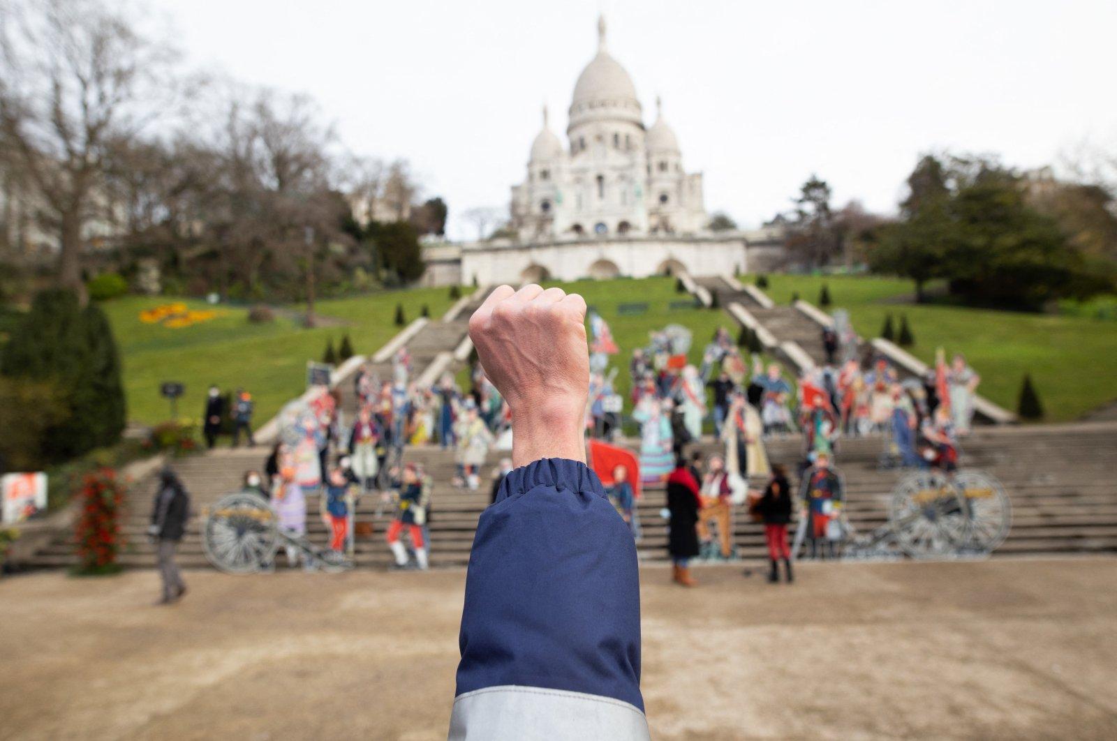 A man raises his fist during the celebration of the 150 year anniversary of La Commune de Paris at the Louise Michel Square next to the Basilica Sacre Coeur, in Paris, France, March 18, 2020. (Photo by Raphael Lafargue/abacapress.com via Reuters)