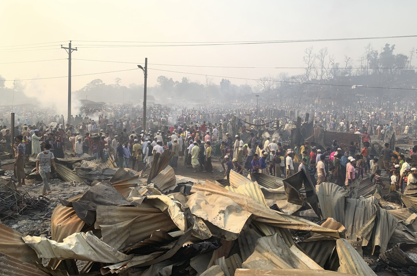 Rohingya refugees look at the remains of Monday's fire at the Rohingya refugee camp in Balukhali, southern Bangladesh, March 23, 2021. (AP Photo)