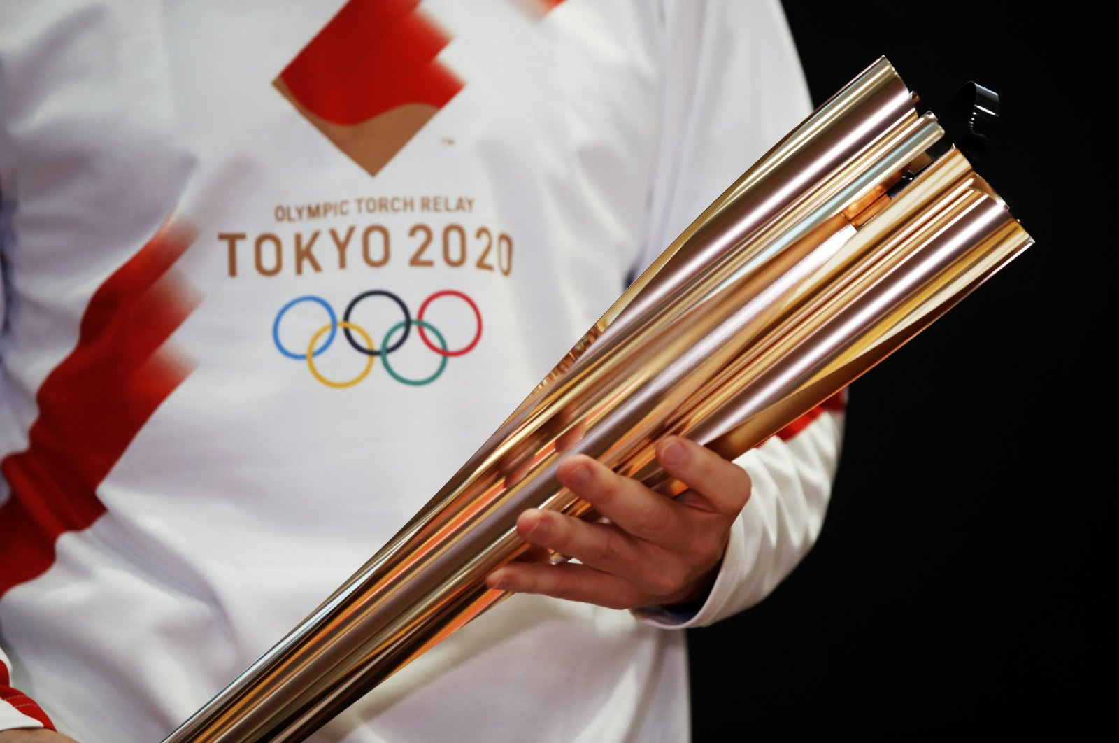 Greek singer Sakis Rouvas wears the uniform of the torch relay runners in Athens, Greece, as he holds the torch of the 2020 Tokyo Olympic Games during a presentation, Feb. 24, 2020. (AP Photo)