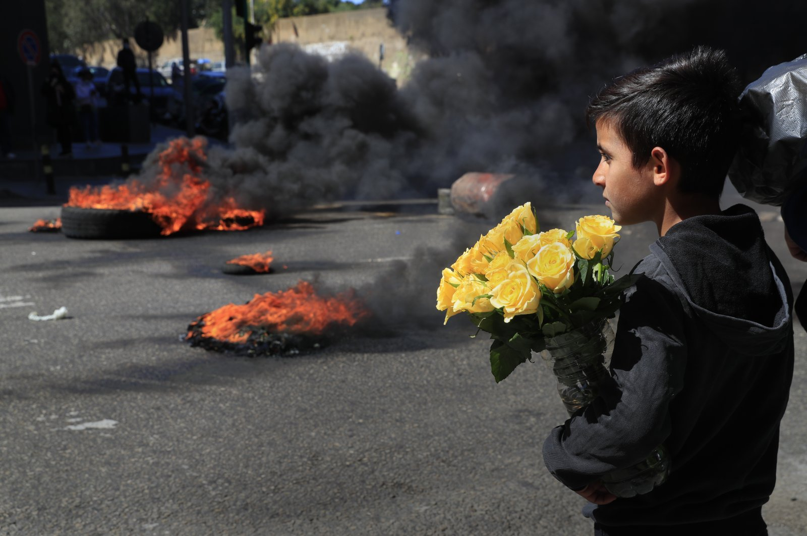 A Syrian boy selling flowers on the street watches protesters burn tires to block a main road during a protest against the increase in prices of consumer goods and the crash of the local currency, in Beirut, Lebanon, March 16, 2021. (AP Photo)
