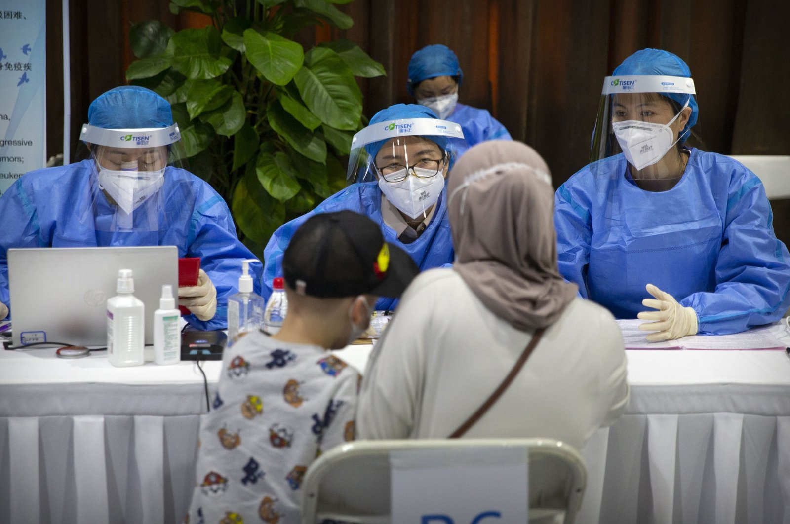 Workers wearing protective gear register a person during a COVID-19 vaccination session for resident foreign journalists at a vaccination center in Beijing, Tuesday, March 23, 2021. (AP Photo)