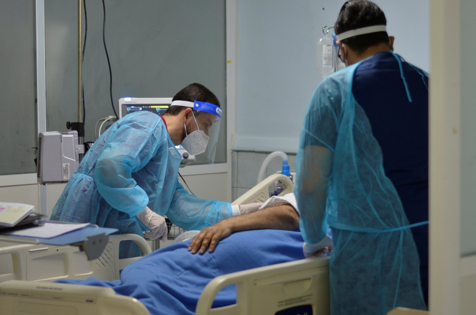 Medical staff members assist a patient suffering from coronavirus disease (COVID-19), in an intensive care unit at a hospital in Amman, Jordan, March 23, 2021.  (REUTERS/Muath Freij)