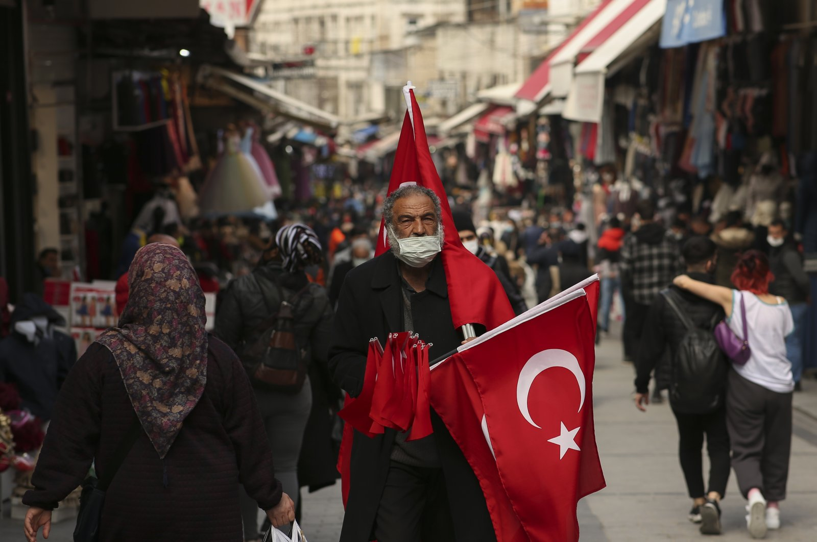 A vendor offers Turklish flags for sale at an open market Istanbul, Monday, March 22, 2021. (AP Photo)