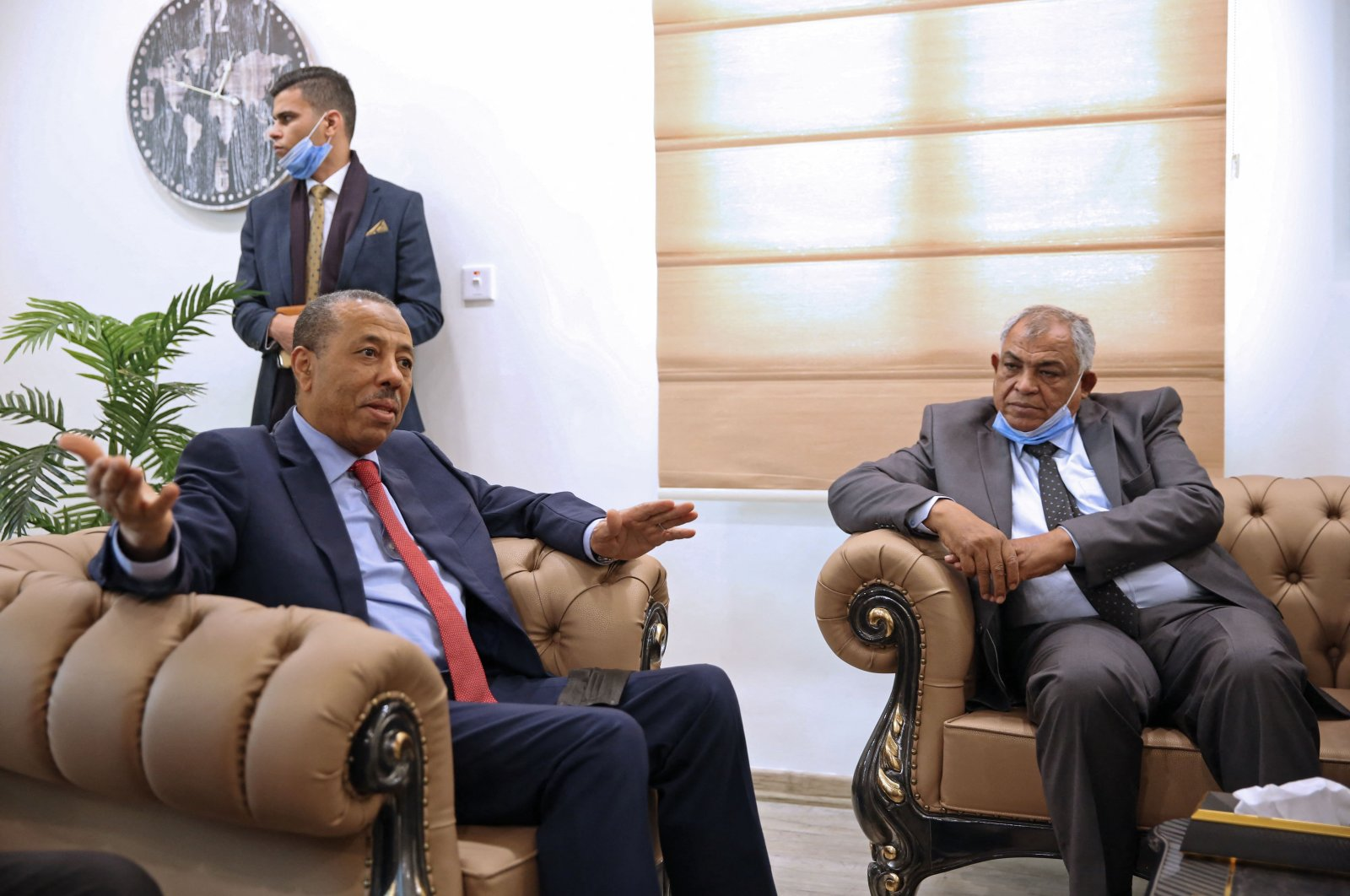 Libya's Deputy Prime Minister in the national unity government, Hussein Attiya al-Gotrani (R), listens to Abdallah al-Thani (L), the former head of the pro-Haftar eastern administration during a handover ceremony in Benghazi, Libya, March 23, 2021. (AFP Photo)