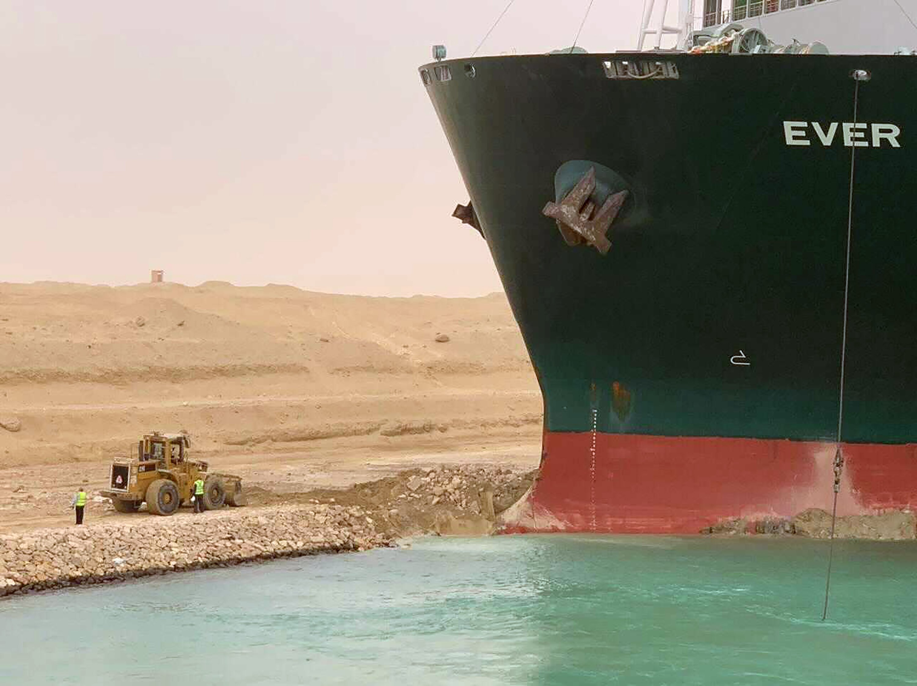 In this photo released by the Suez Canal Authority, a cargo ship, named the Ever Green, sits with its bow stuck into the wall Wednesday, March 24, 2021, after it turned sideways in Egypt's Suez Canal. (Suez Canal Authority via AP)