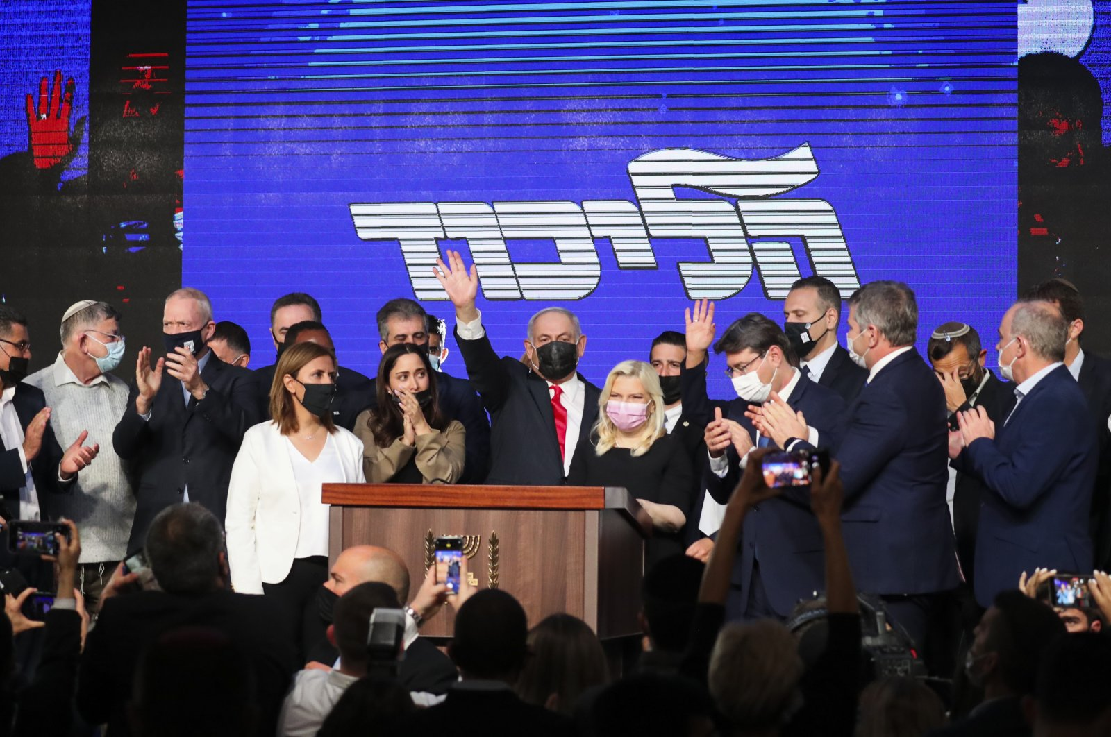 Israeli Prime Minister Benjamin Netanyahu, center, wearing a protective face mask, waves after delivering a speech to supporters following the announcement of exit polls of the Israeli parliamentary elections at his party's headquarters in Jerusalem, Wednesday, March. 24, 2021. (AP Photo)