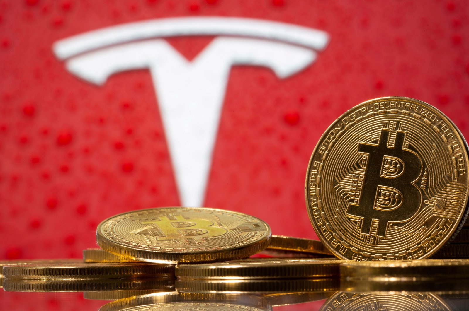 Representations of the virtual currency bitcoin in front of the Tesla logo in this illustration, Feb. 9, 2021. (Reuters Photo)
