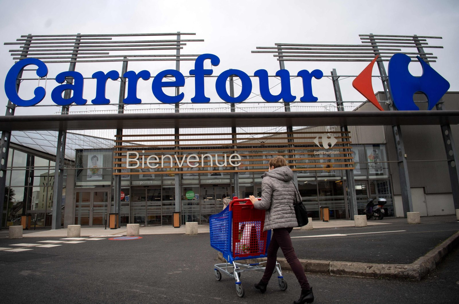A woman enters a French retail giant Carrefour supermarket in Saint-Herblain, outside Nantes, France, Jan. 13, 2021. (AFP Photo)