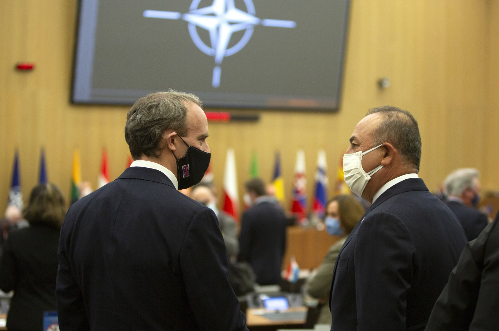 British Foreign Secretary Dominic Raab (L) speaks with Turkish Foreign Minister Mevlut Cavusoglu (R) during a meeting of NATO foreign ministers at NATO headquarters, Brussels, Belgium, March 23, 2021. (EPA)