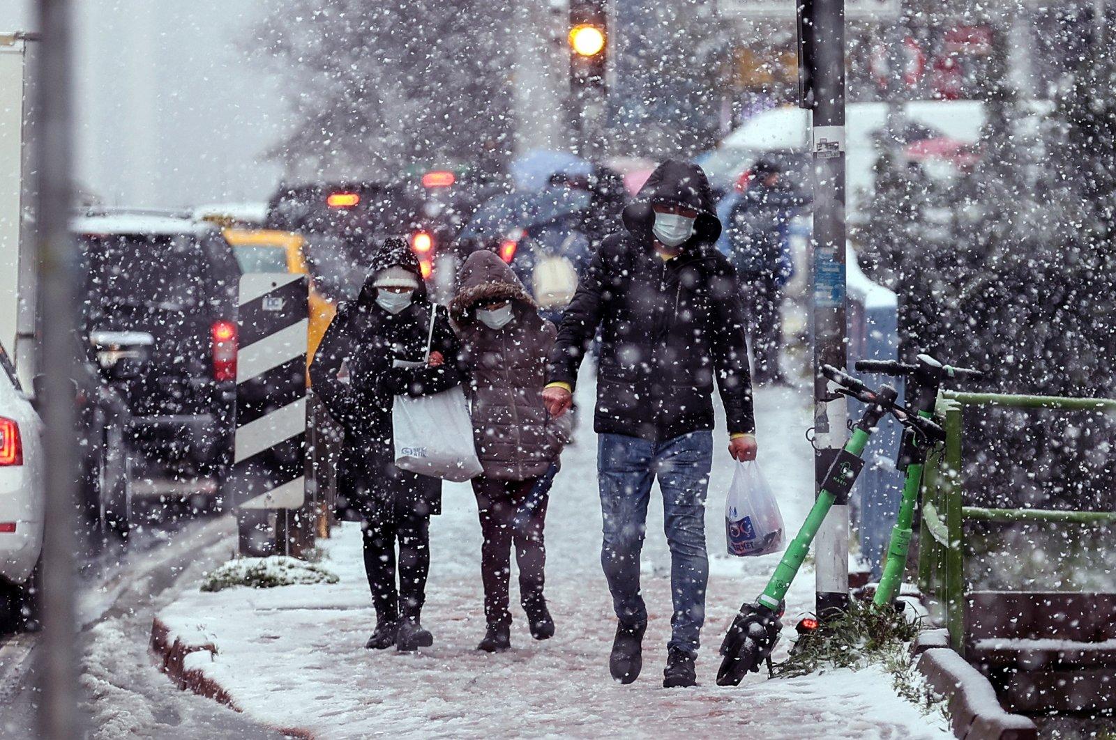 People walk in a street as heavy snowfall hits the Okmeydanı neighborhood in Istanbul, Turkey, March 24, 2021. (AA PHOTO)