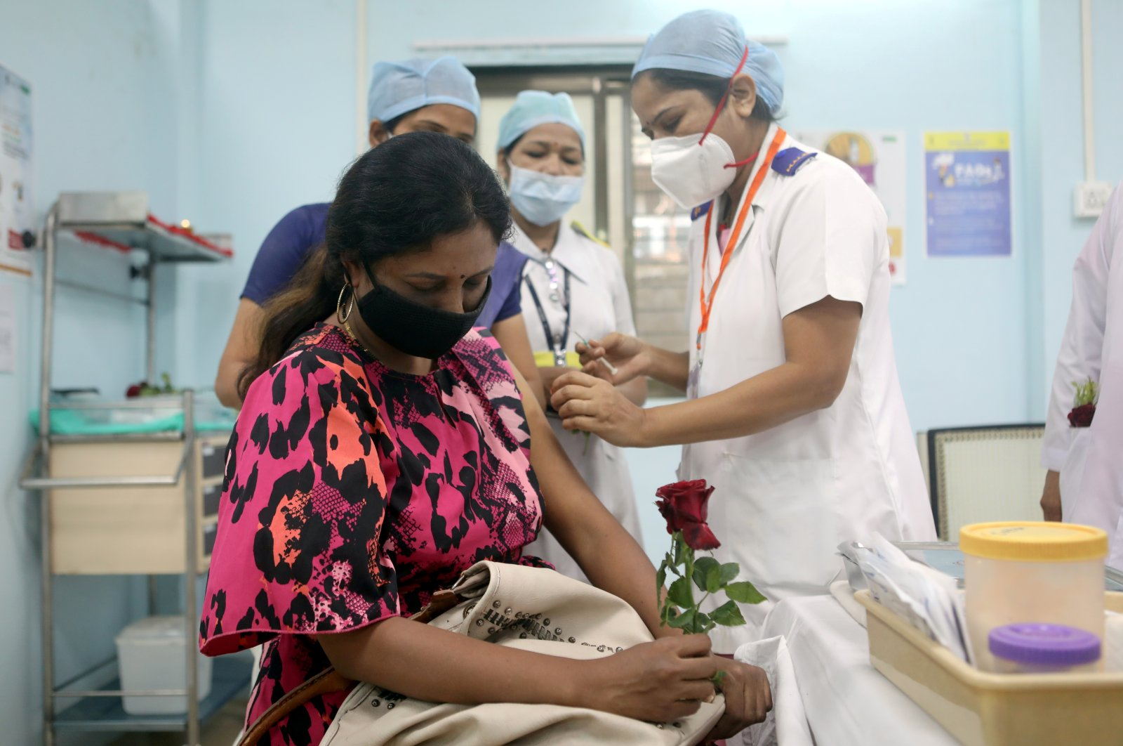 A health care worker holding a rose receives AstraZeneca's COVISHIELD vaccine at a medical center during the coronavirus vaccination campaign, Mumbai, India, Jan. 16, 2021. (Reuters Photo)