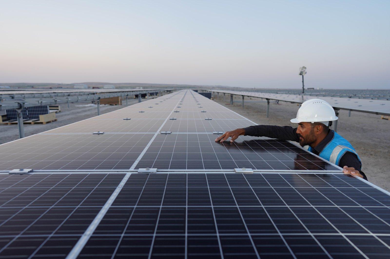 An employee works next to the solar power panels in the Karapınar Solar Power Plant, Konya, central Turkey, Sept. 29, 2020. (IHA Photo)