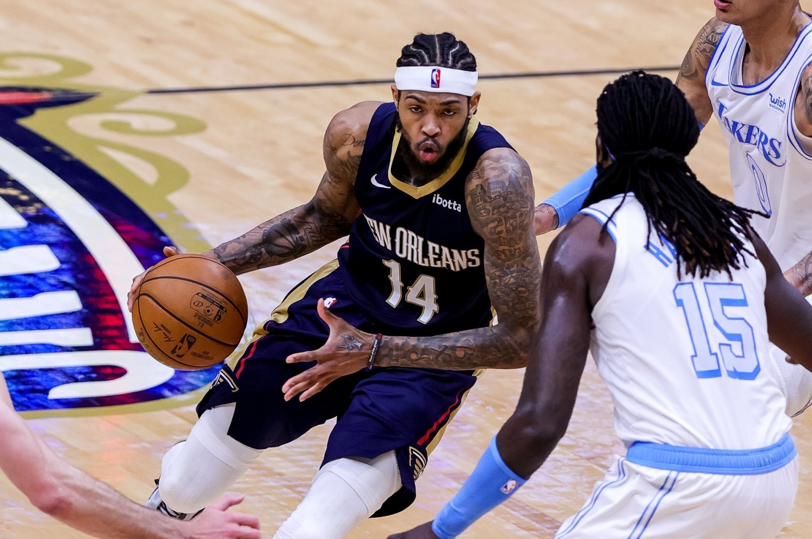 New Orleans Pelicans forward Brandon Ingram (L) dribbles against Los Angeles Lakers center Montrezl Harrell (R) during an NBA game at Smoothie King Center, New Orleans, Louisiana, U.S.,  March 23, 2021.