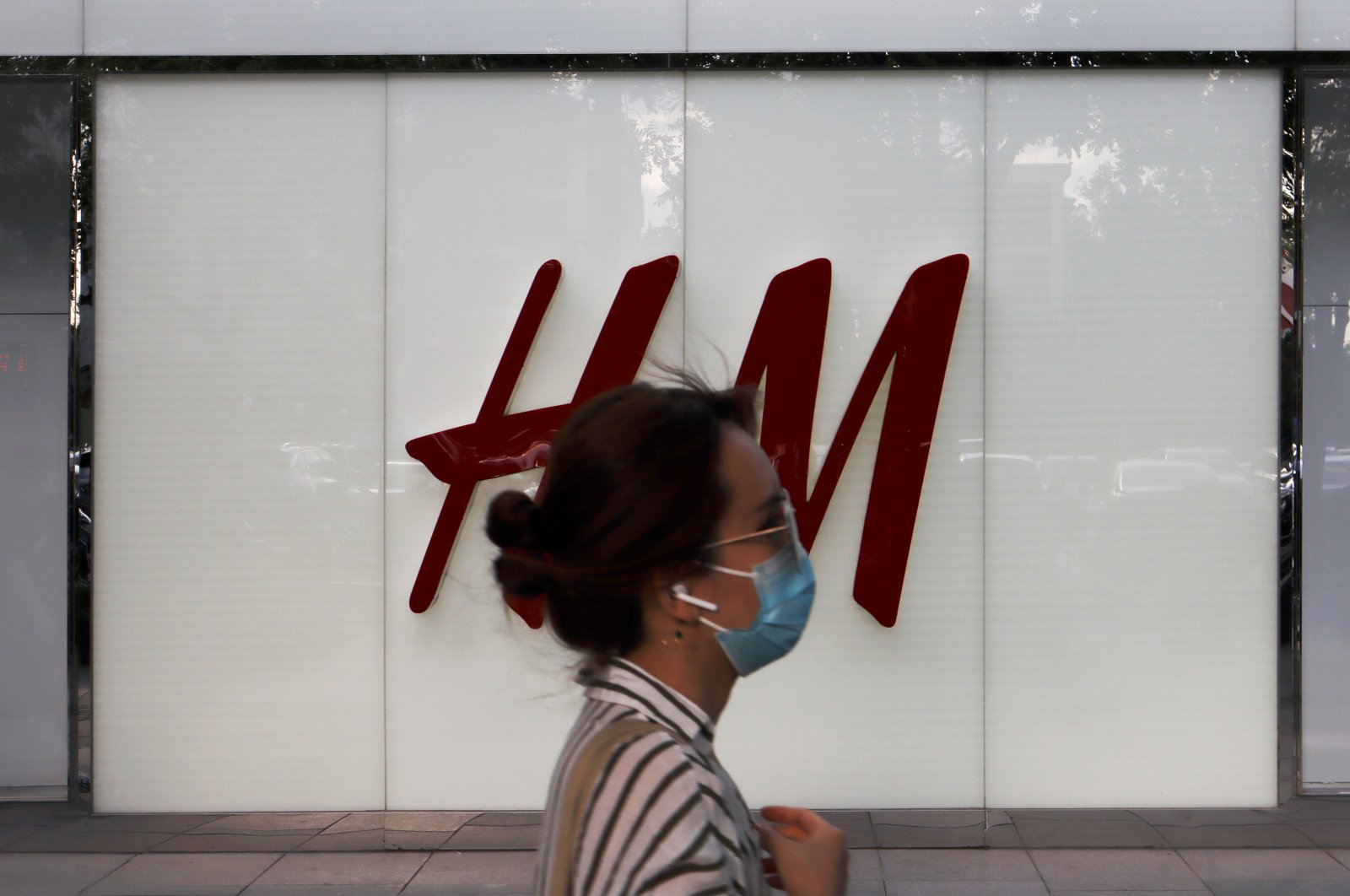 A woman walks past a store of the Swedish fashion retailer H&M at a shopping complex in Beijing, China, May 24, 2020. (Reuters Photo)