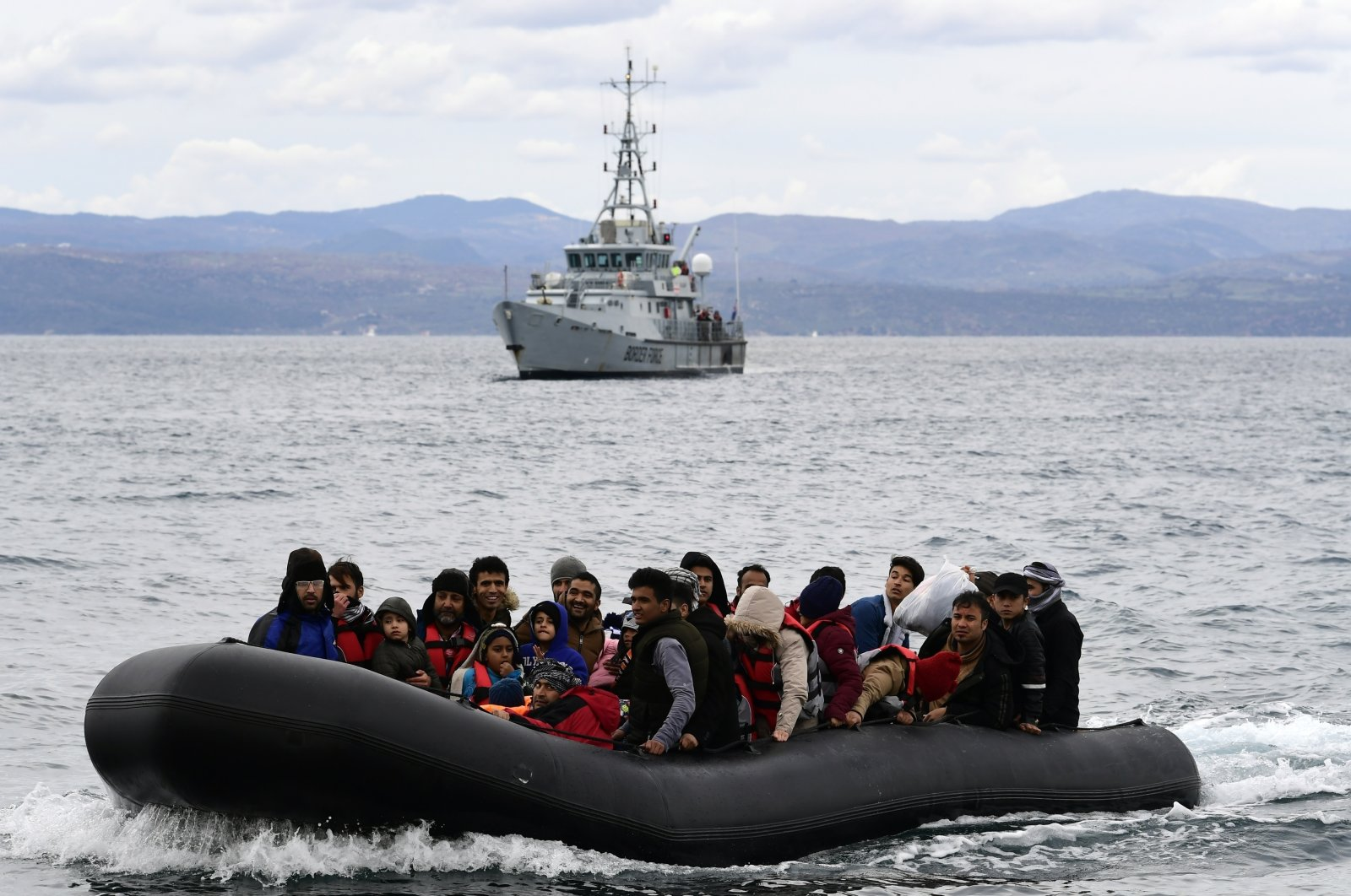 Migrants arrive aboard a dinghy accompanied by a Frontex vessel at the village of Skala Sikaminias, on the Greek island of Lesbos, after crossing the Aegean sea from Turkey, Feb. 28, 2020. (AP Photo)