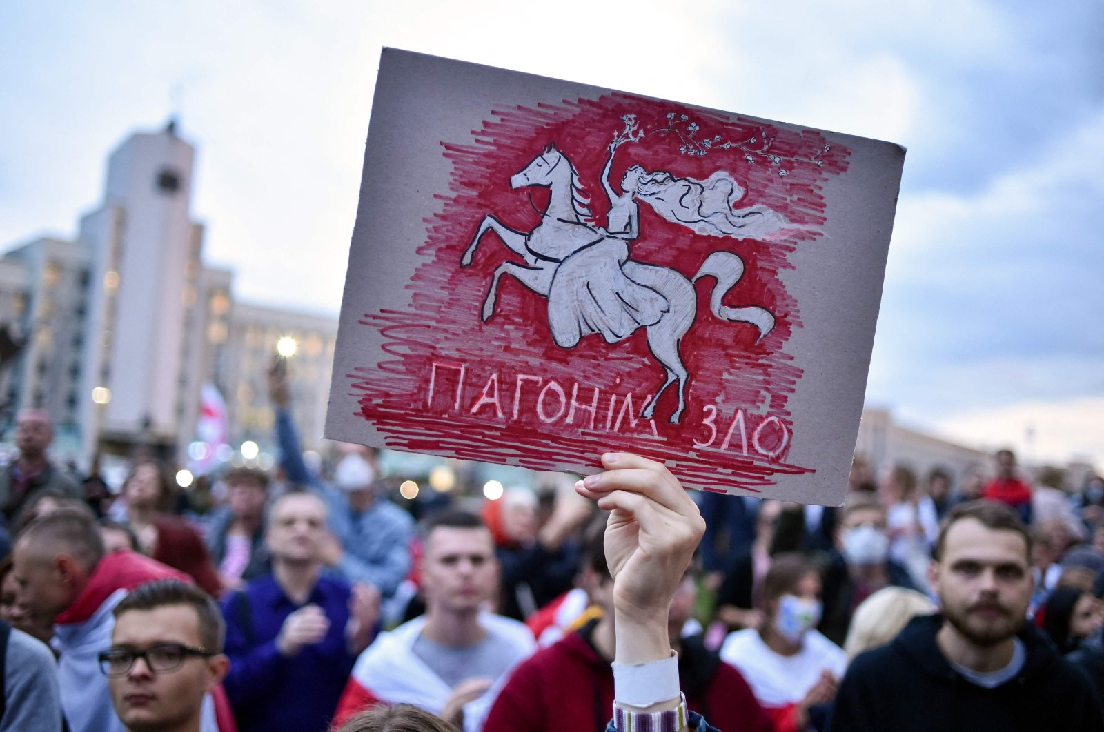 """A demonstrator holding up a placard reading """"Drive away evil"""" attends a rally of opposition supporters to protest against disputed presidential elections results, Minsk, Belarus, Aug. 25, 2020. (AFP Photo)"""