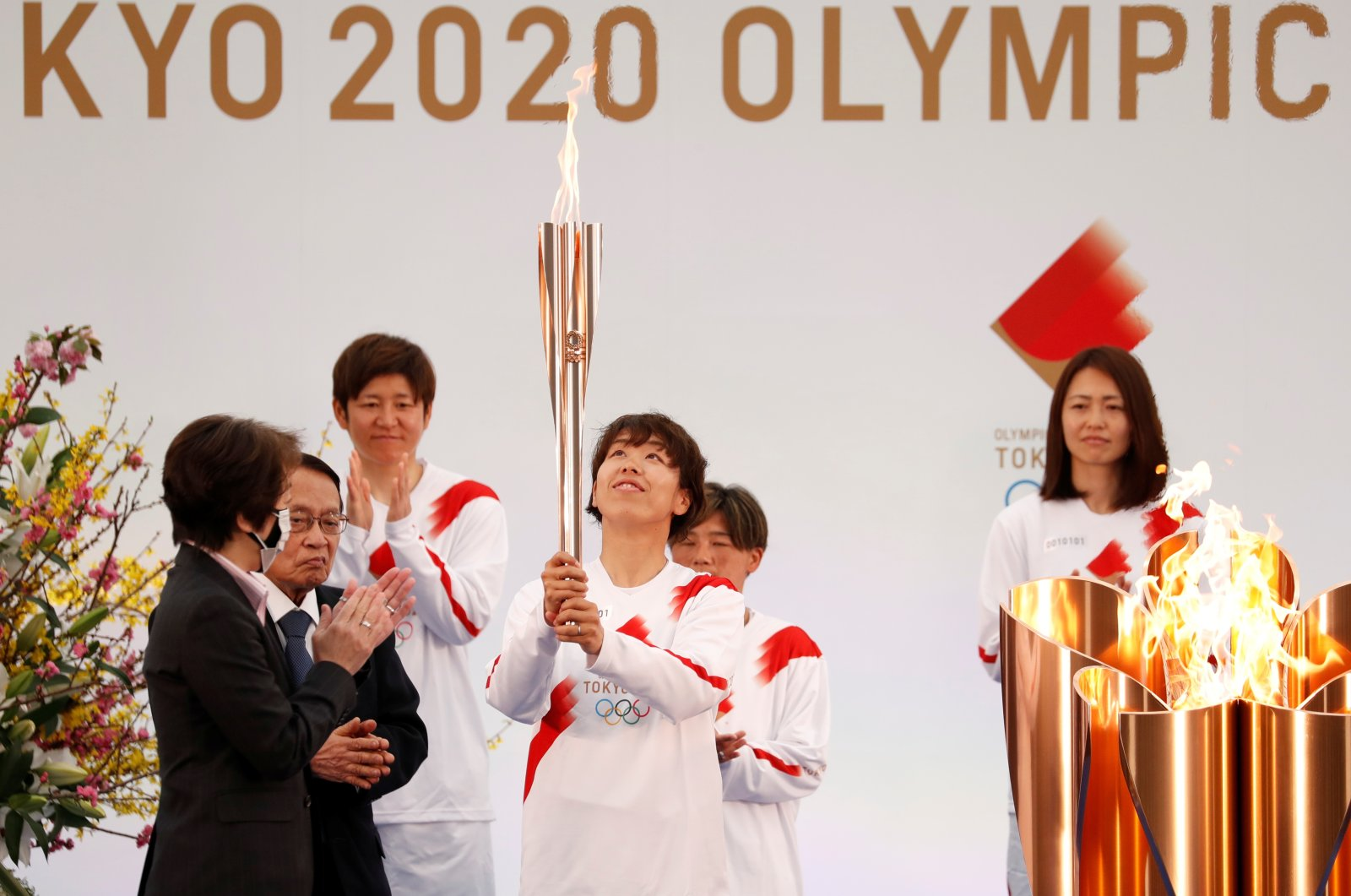 A member of Japan's women's national football team carries the torch during the Tokyo 2020 Olympic Torch Relay Grand Start in Naraha, Japan, March 25, 2021. (Reuters Photo)