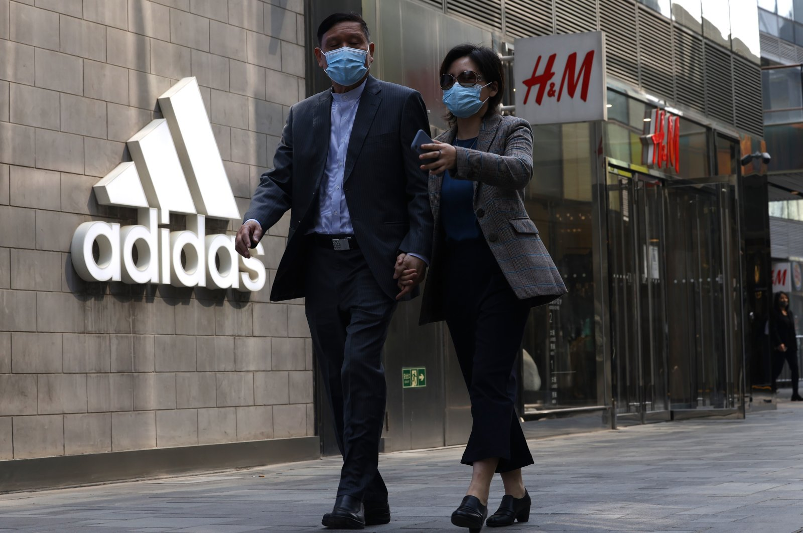 People walk by Adidas and H&M stores in Beijing, China, March 25, 2021. (AP Photo)