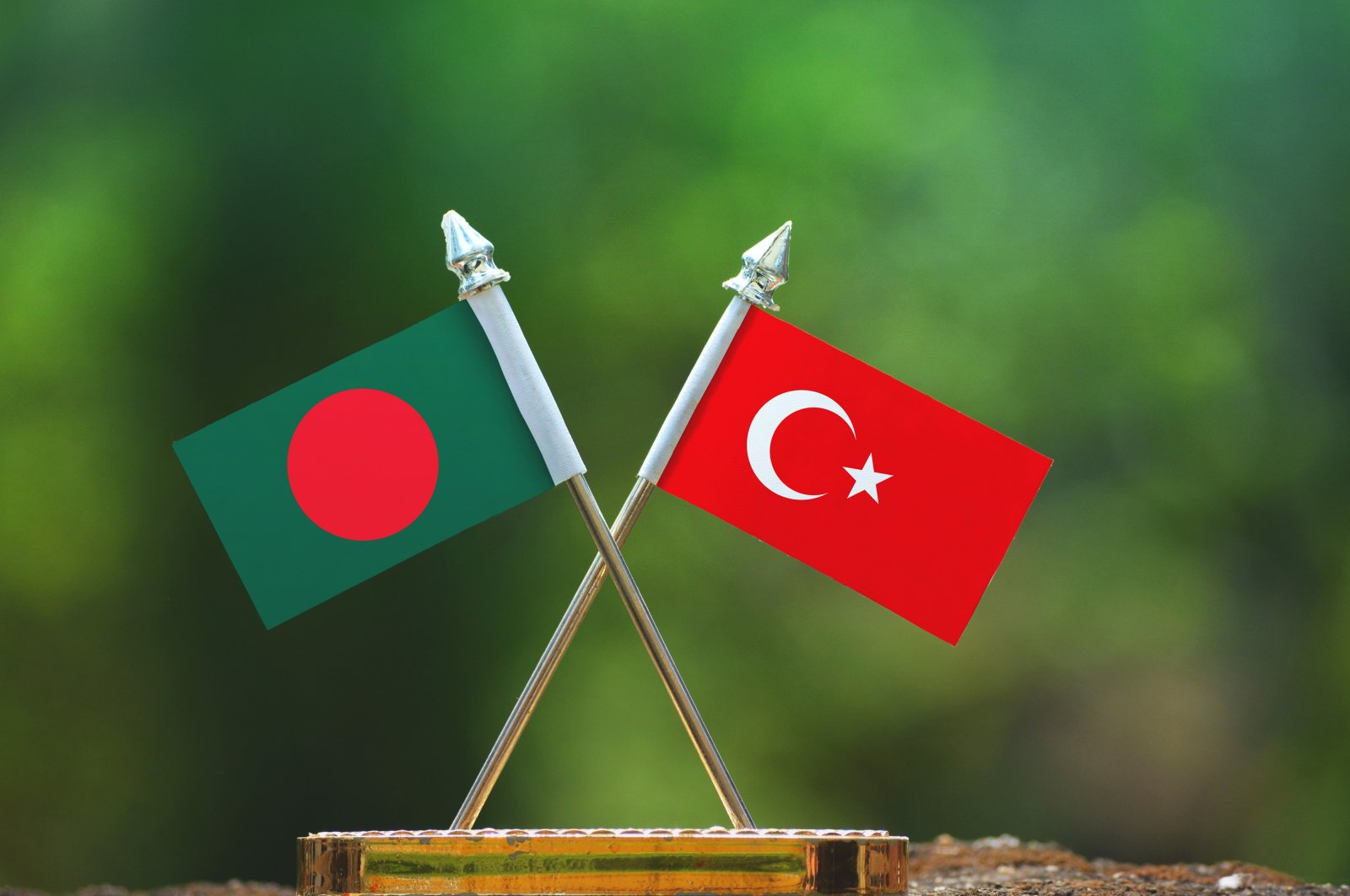In this photo illustration, the flags of Bangladesh and Turkey are seen together with a blurred green background. (Photo by Shutterstock)